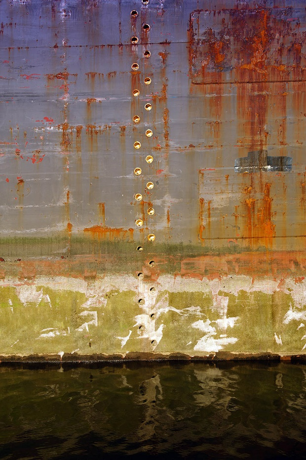Rusty hull of a ship docked in The Brooklyn Navy Yard